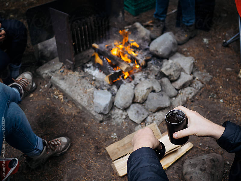 Young man holding coffee mug near campfire while camping by Jeremy Pawlowski for Stocksy United