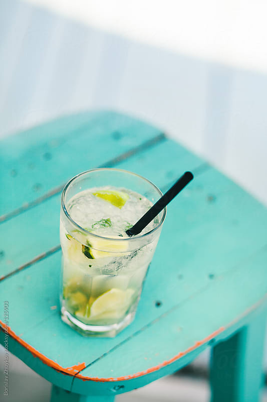 Summer cocktail - gin & tonic - on a color wooden vintage chair by Borislav Zhuykov for Stocksy United