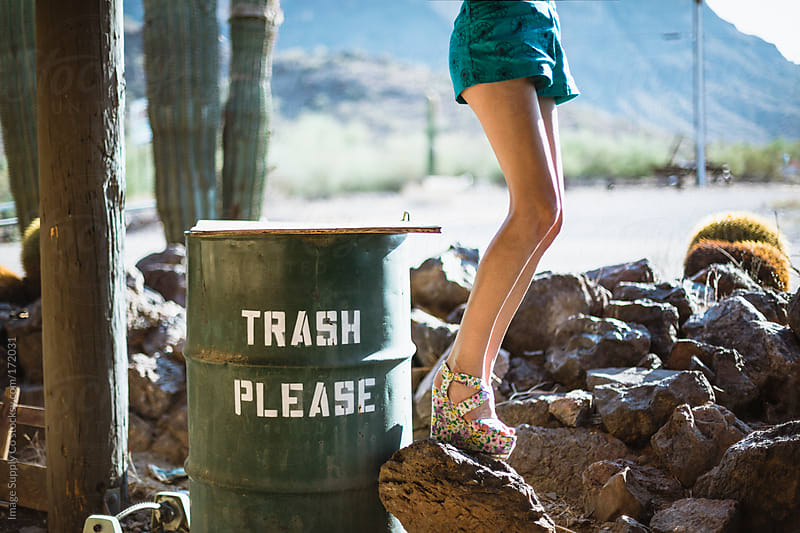 Trash can and girls legs by Image Supply Co for Stocksy United