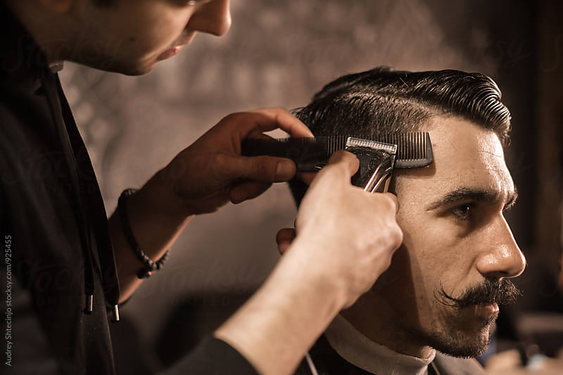 close up of barber working on client hair in barber shop by Marko Milanovic for Stocksy United