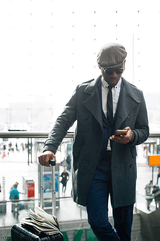 Portrait of Well-Dressed Young Black Businessman Using Cellphone in Bright Public Space by VISUALSPECTRUM for Stocksy United