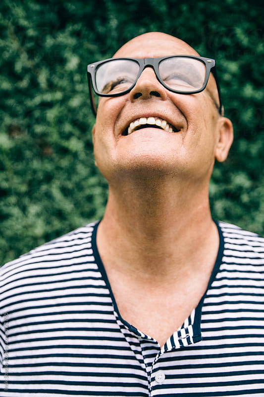 Senior man laughing portrait wearing glasses and marine stripe tshirt by Inuk Studio for Stocksy United
