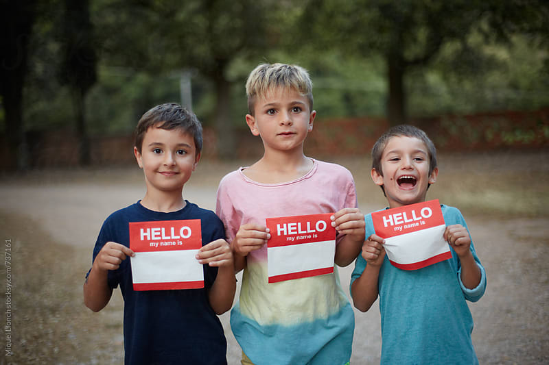 Three kids with napkins for introducing yourself by Miquel Llonch for Stocksy United