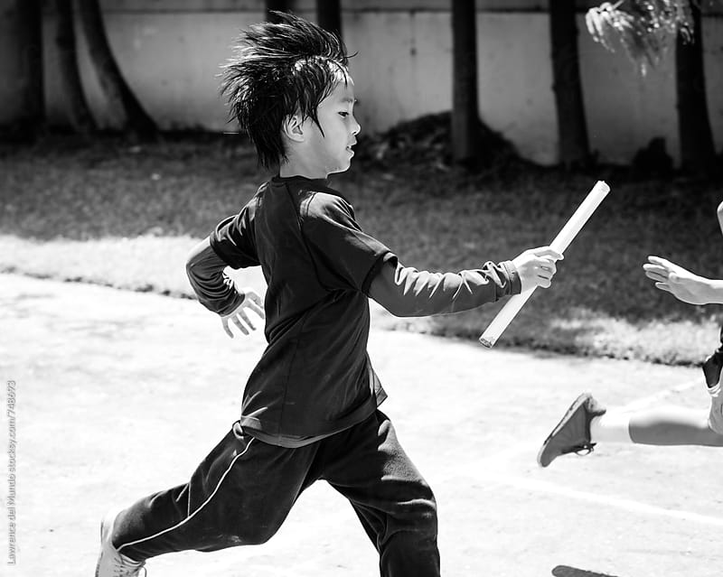 Young kid running the relay race and passing the baton to his teammate by Lawrence del Mundo for Stocksy United