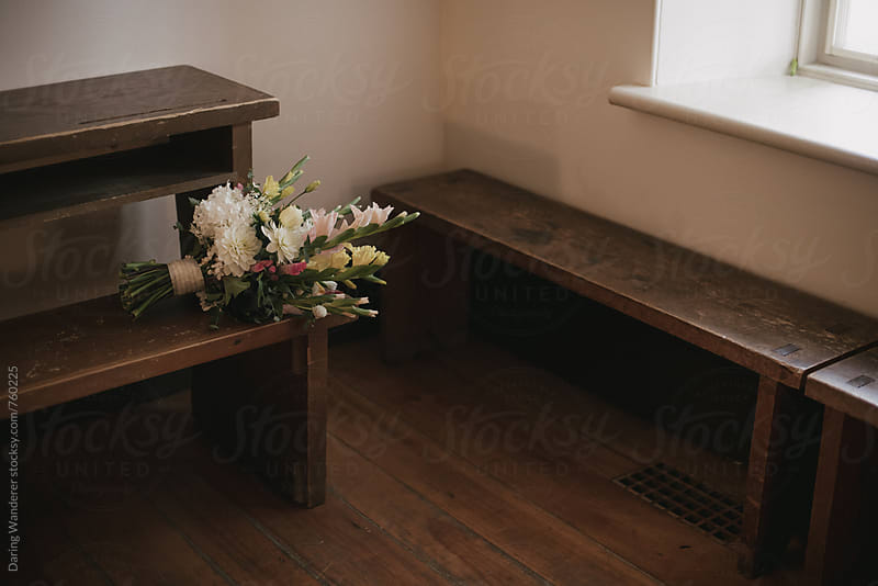 Bridal bouquet and flowers on wood bench in old school house wedding venue by Daring Wanderer for Stocksy United
