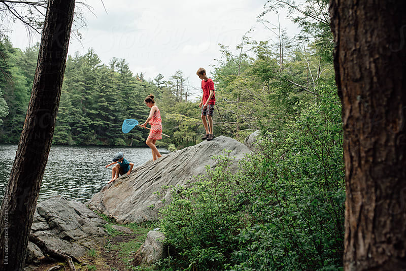 three kids on a rock by a lake by Léa Jones for Stocksy United