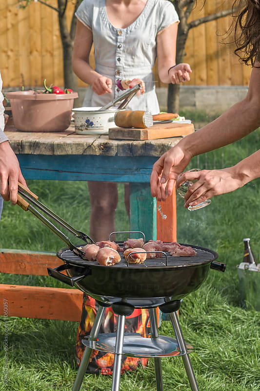 Friends making barbecue outdoor by RG&B Images for Stocksy United