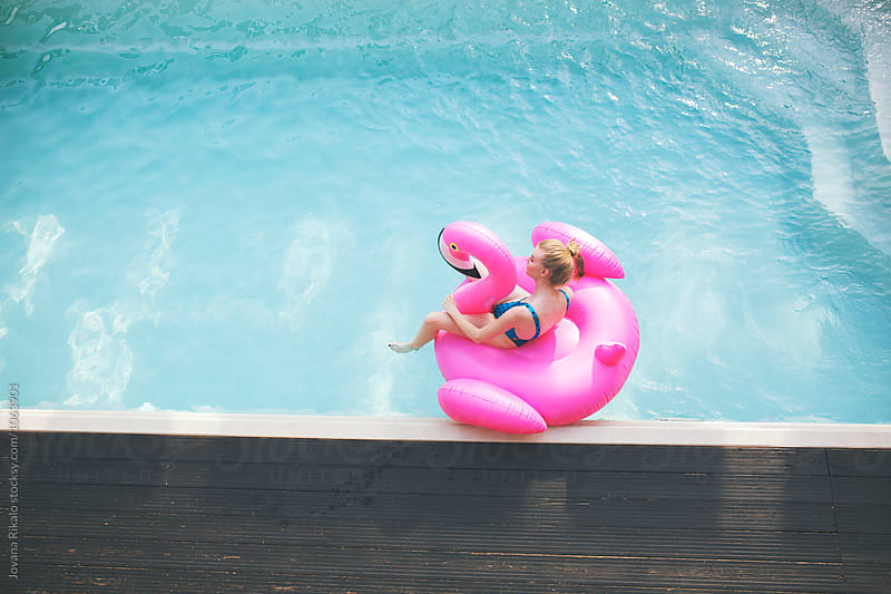 Beautiful young woman floating on a flamingo float in a swimming pool by Jovana Rikalo for Stocksy United