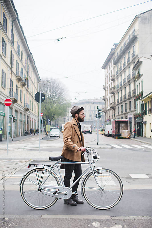 Young hipster walking with bicycle in the city by michela ravasio for Stocksy United