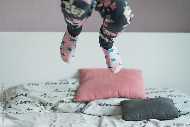 child enjoying in the bed at morning by Javier Pardina for Stocksy United