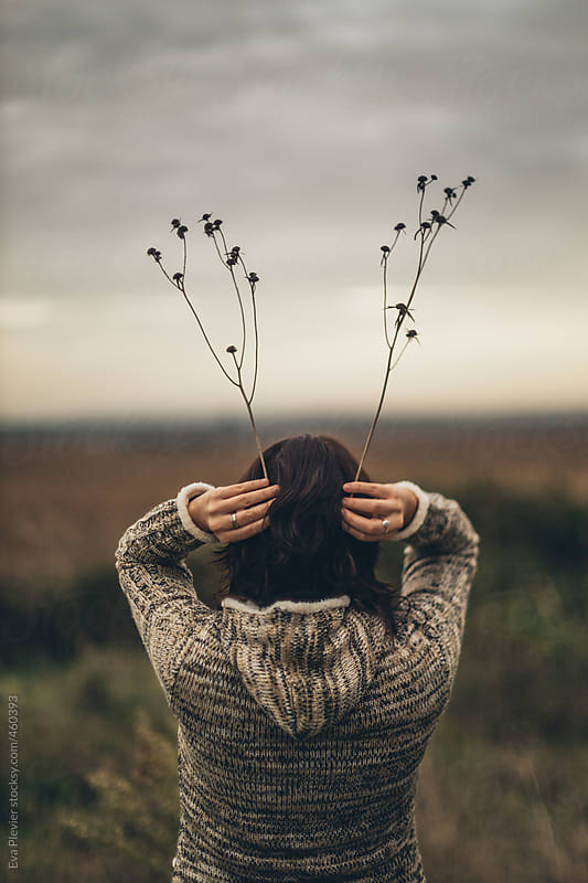 Young woman holing branches above her head. by Eva Plevier for Stocksy United