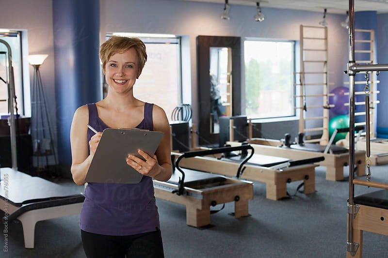 Business owner in her fitness and Pilates studio by Edward Bock for Stocksy United