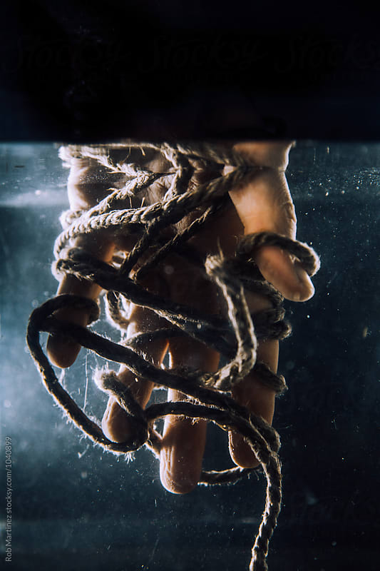 TIED UP HAND UNDERWATER by Rob Martinez for Stocksy United