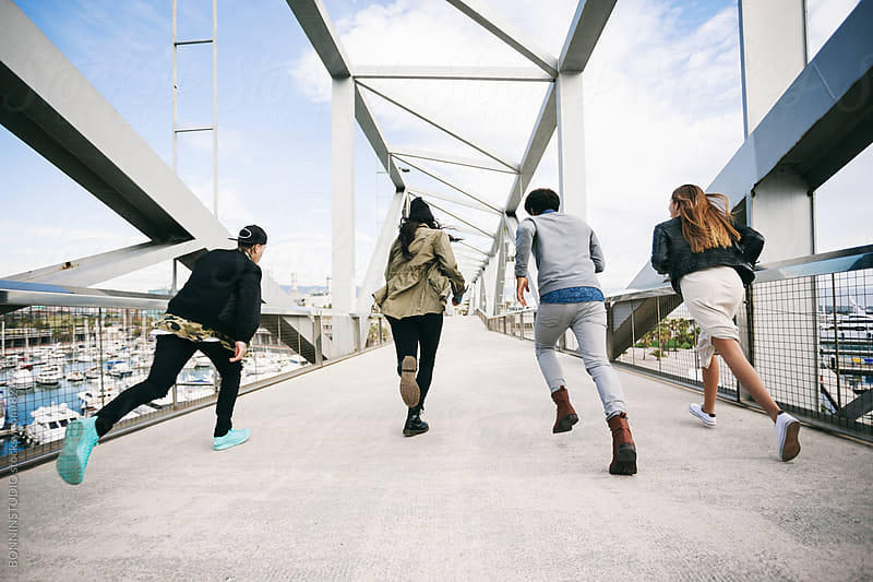 Back view of group of friends running on a modern bridge. by BONNINSTUDIO for Stocksy United