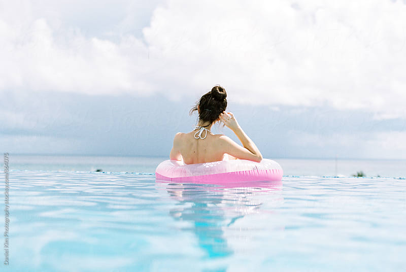 Woman floating in pool tube by Daniel Kim Photography for Stocksy United