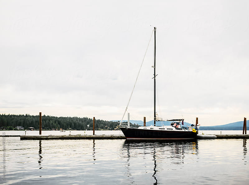 Yacht sails near pier in Idaho by Trent Lanz for Stocksy United