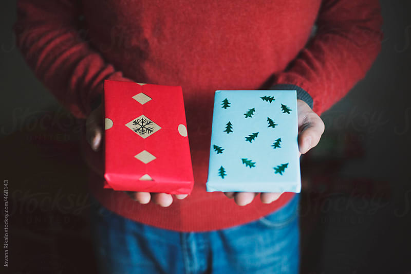 Man holding Christmas gifts by Jovana Rikalo for Stocksy United