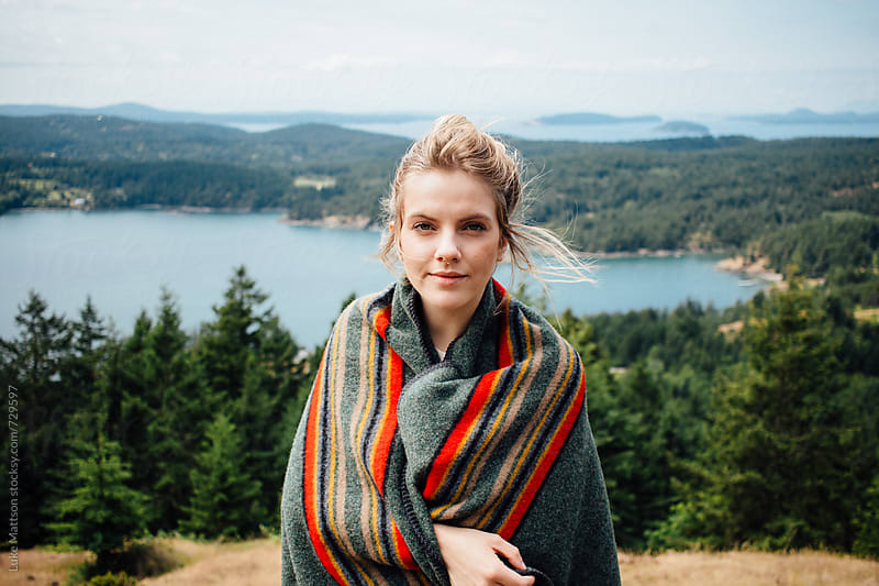 Young Blonde Woman Wrapped In Wool Blanket On Forest Island Hillside  by Luke Mattson for Stocksy United