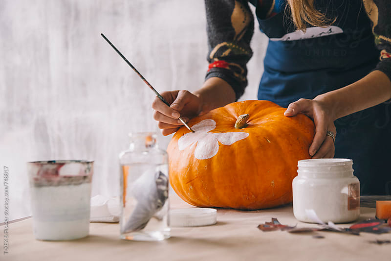 Woman painting pumpkin with brush and white gouache by Danil Nevsky for Stocksy United