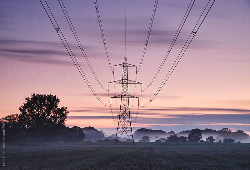 Sweeping clouds over an electricity pylon at twilight. Norfolk, UK. by Liam Grant for Stocksy United