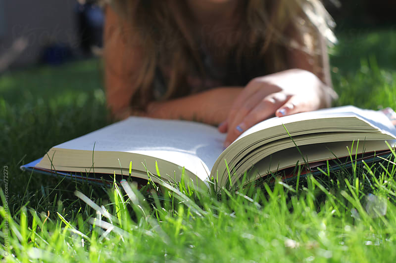 Young girl laying in the grass, reading a book by Carolyn Lagattuta for Stocksy United