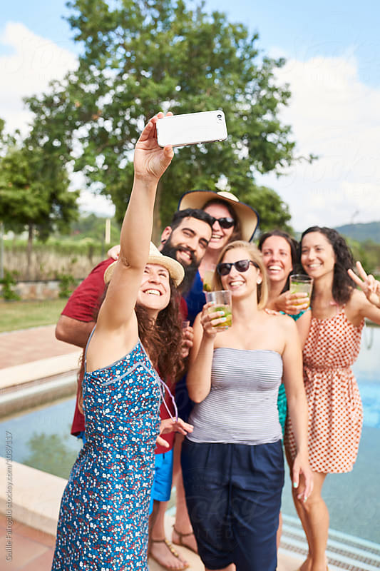 Friends making selfie against of pool in garden by Guille Faingold for Stocksy United