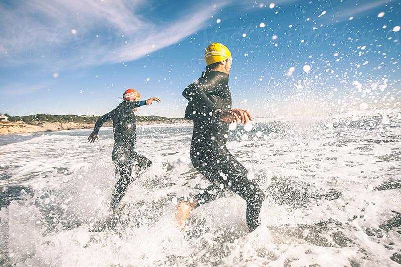Two triathletes running to the water on triathlon race. Splashing water. by BONNINSTUDIO for Stocksy United