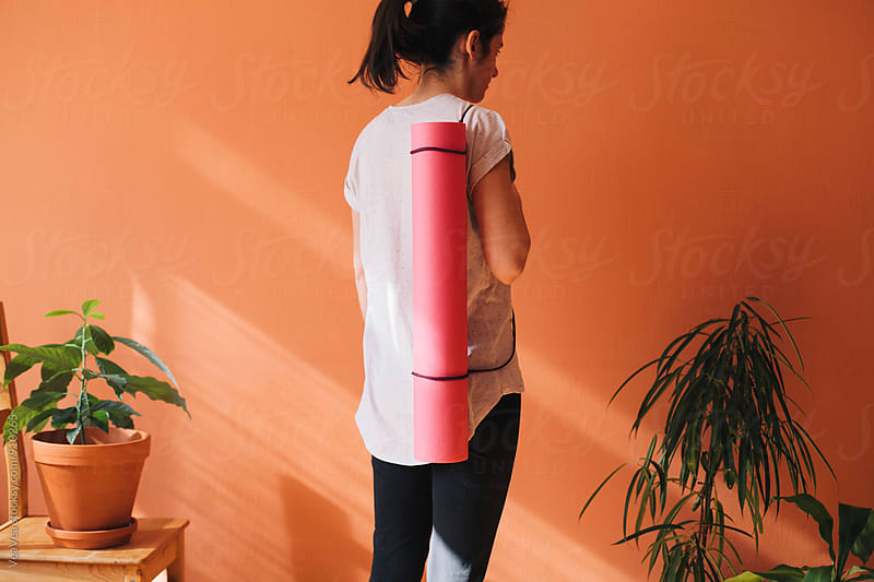 Woman holding a fitness mat by VeaVea for Stocksy United