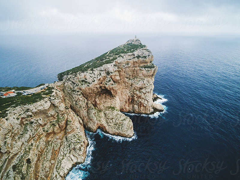 Aerial view of a lighthouse on a cliff by Luca Pierro for Stocksy United