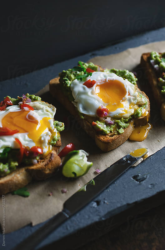 Guacamole on toast with fried egg. by Darren Muir for Stocksy United
