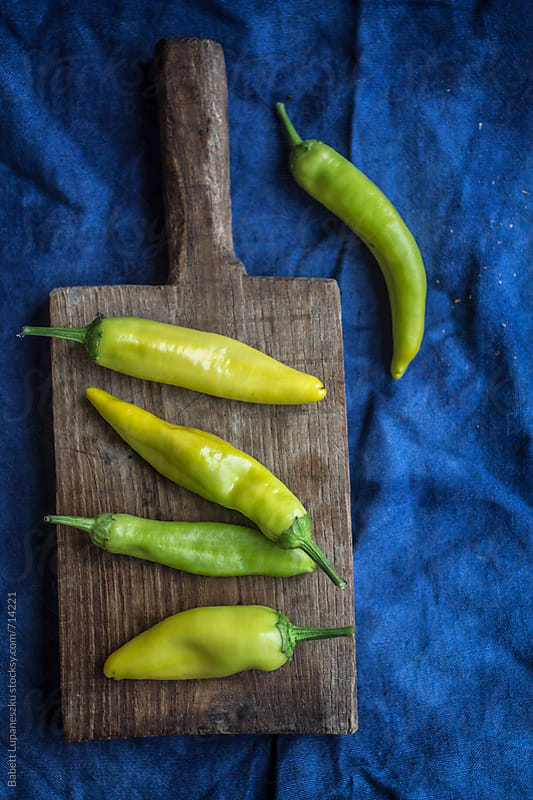 hot peppers on cutting board by Babett Lupaneszku for Stocksy United