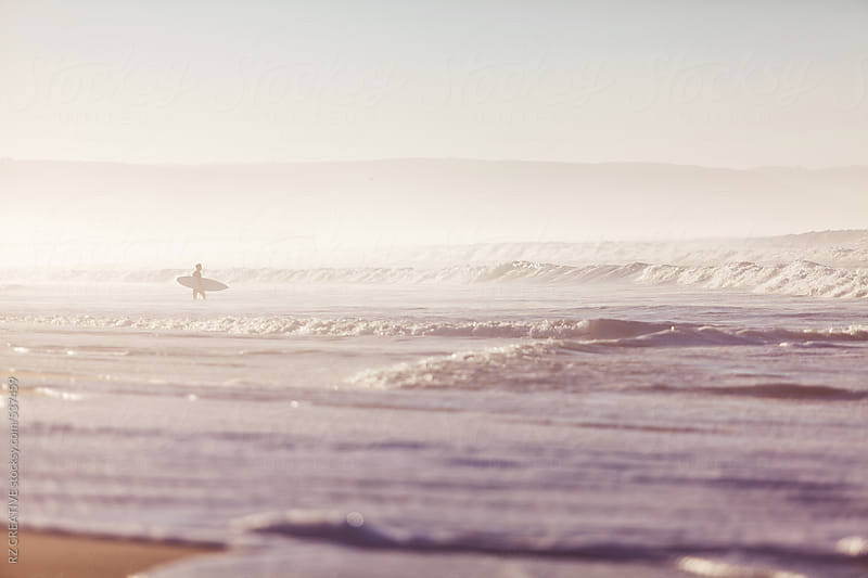 A lone surfer enters the ocean at sunrise. by RZ CREATIVE for Stocksy United