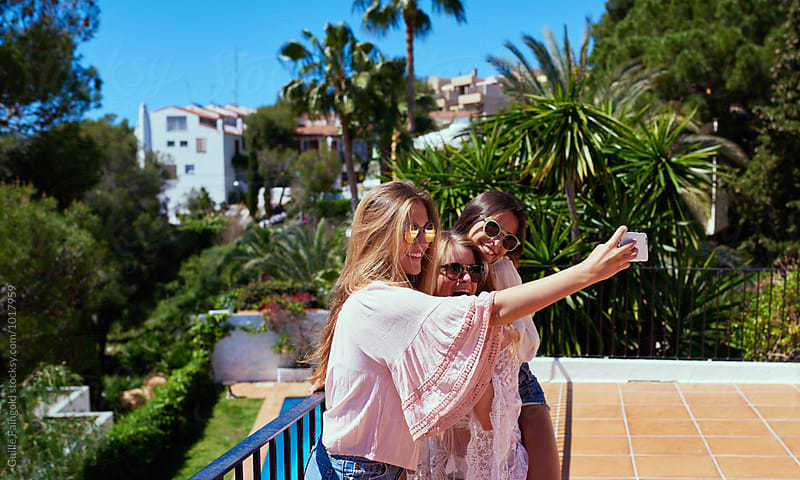 Smiling girls taking selfie in garden by Guille Faingold for Stocksy United