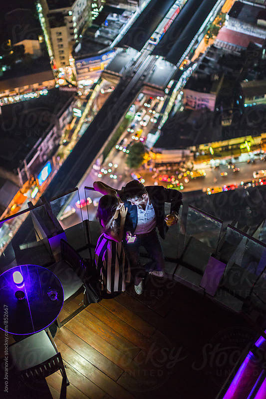 Aerial view of a stylish and fashionable young couple on a date in a modern rooftop lounge city bar  by Jovo Jovanovic for Stocksy United