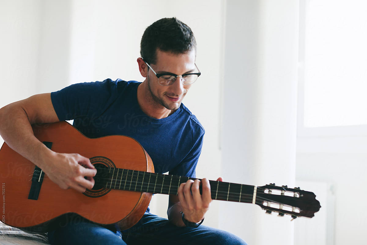 young man playing guitar at home stocksy united. Black Bedroom Furniture Sets. Home Design Ideas