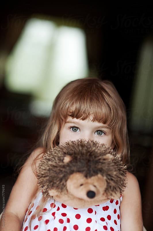Little girl with a toy bunny (hedgehog) by Sveta SH for Stocksy United