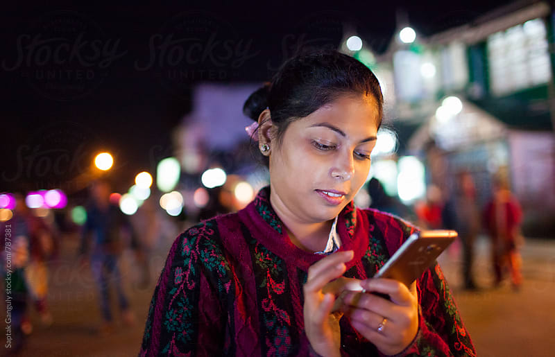 Young woman using mobile phone in the street at night by Saptak Ganguly for Stocksy United