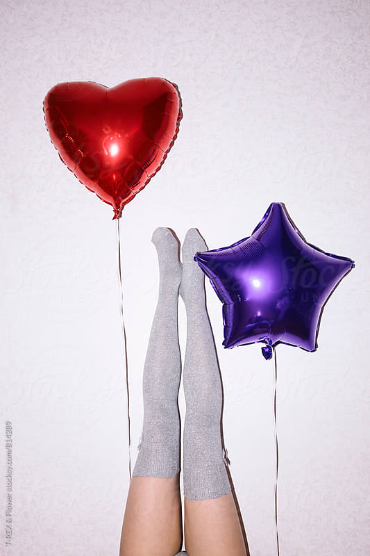Two red and blue balloons with woman's legs against of wall by Danil Nevsky for Stocksy United