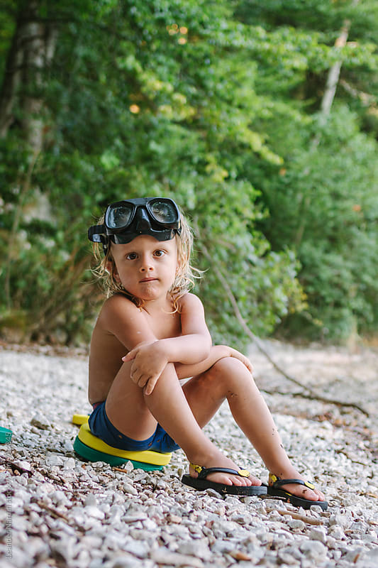 cute toddler with diving goggles sitting on the shore of a lake by Leander Nardin for Stocksy United