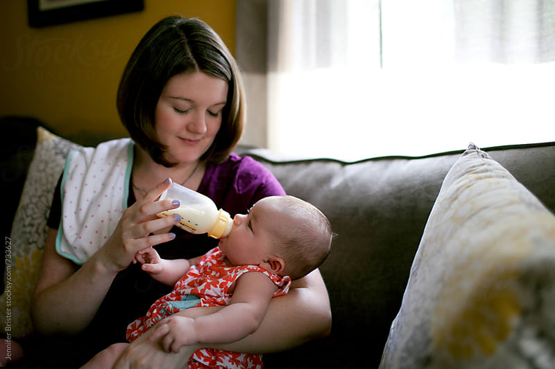New mom feeding baby by Jennifer Brister for Stocksy United