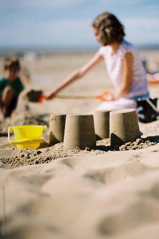 Girl making a sandcastle by Kirstin Mckee for Stocksy United