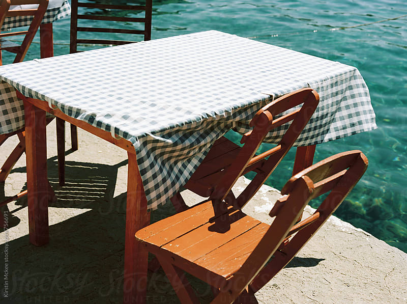 Table and chairs in harbour, Greece by Kirstin Mckee for Stocksy United