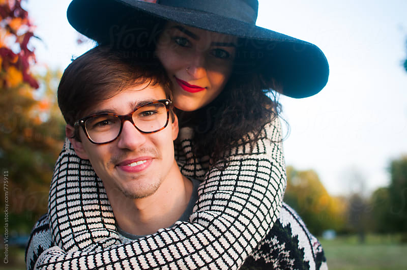 A young couple on a piggyback ride on a fall day by Chelsea Victoria for Stocksy United