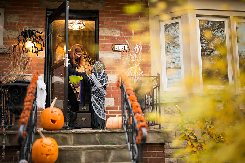 Boy Wearing Scary Halloween Costume Knocking on Front Door Trick or Treat by JP Danko for Stocksy United