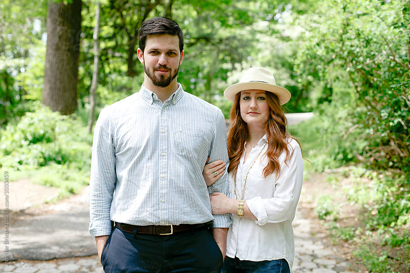 Couple stands in park  by Jennifer Brister for Stocksy United