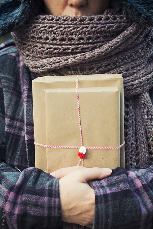 Woman holding gift by Pixel Stories for Stocksy United