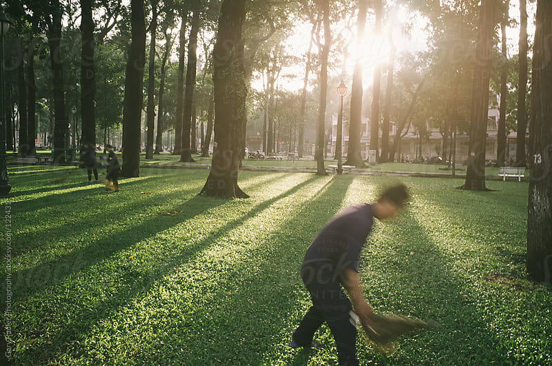 Workers sweeping a Park in Ho Chi Minh City (Saigon) by Gary Radler Photography for Stocksy United