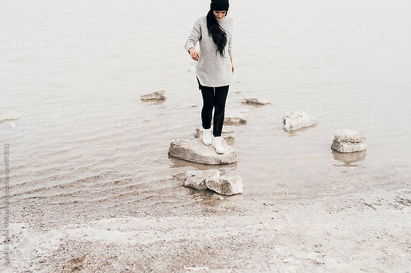 Woman hopping on rocks by Isaiah & Taylor Photography for Stocksy United