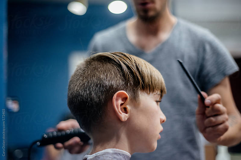 Boy gets a funky haircut at a barber shop by Cara Dolan for Stocksy United
