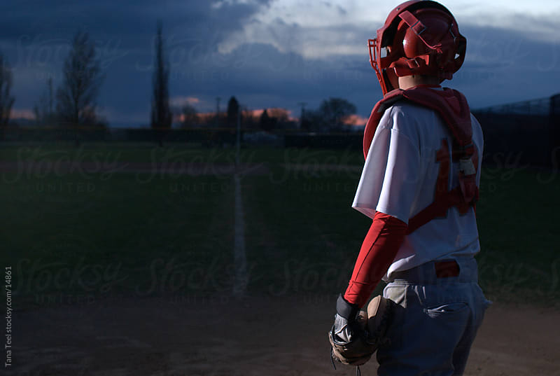 Baseball catcher looking down to first base.  by Tana Teel for Stocksy United